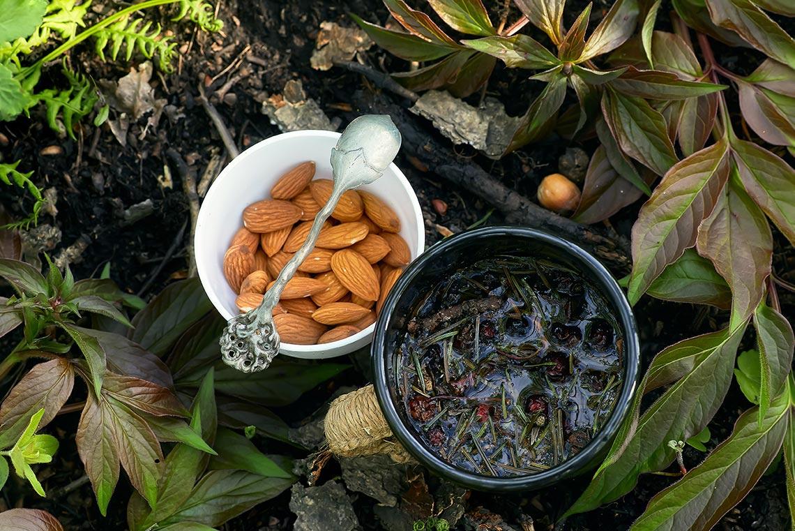Травяной чай с лесными ягодами рядом с кружкой с орехами и ложкой (всё это на фоне земли и листвы)