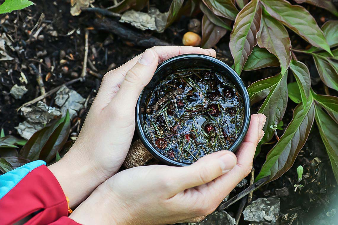 Травяной чай в кружке в руках крупным планом на фоне травы и земли