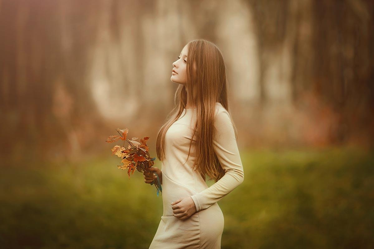 Тонированный портрет девушки с букетом осенних листьев