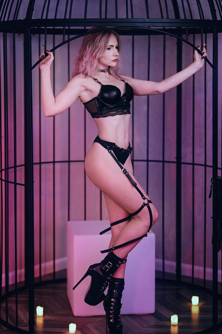 Фото девушки в белье, стоящей в клетке с неоновой розовой подсветкой