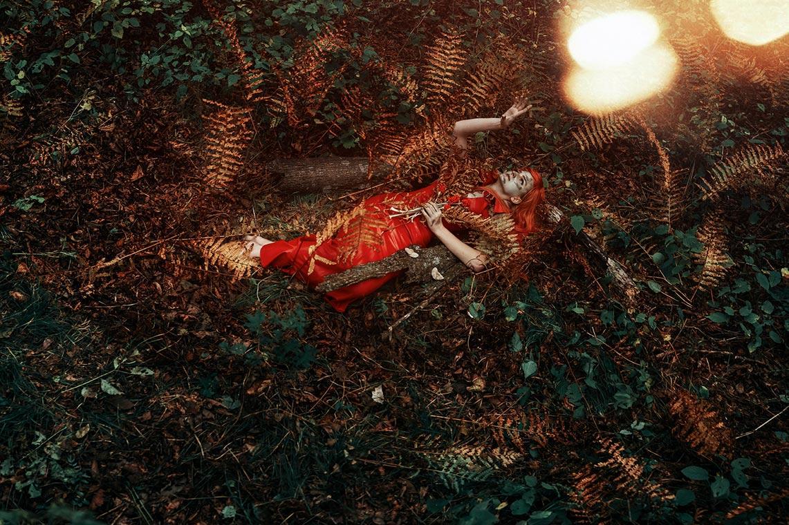 Мрачный осенний полноростовой портрет с девушкой, лежащей в папоротнике