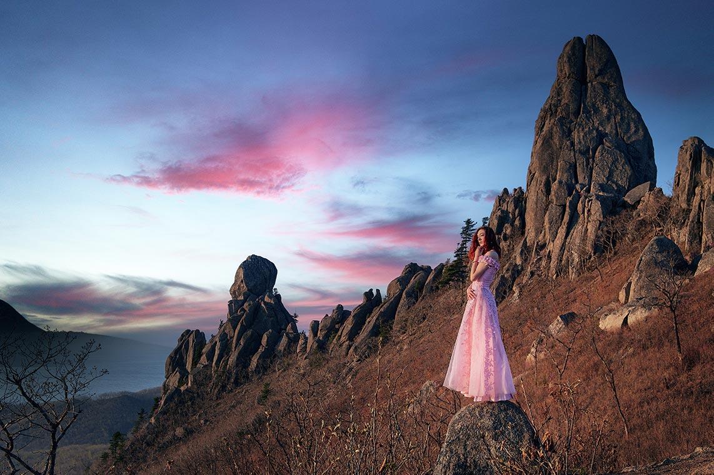 Красивая девушка на фоне гор и рассветных облаков