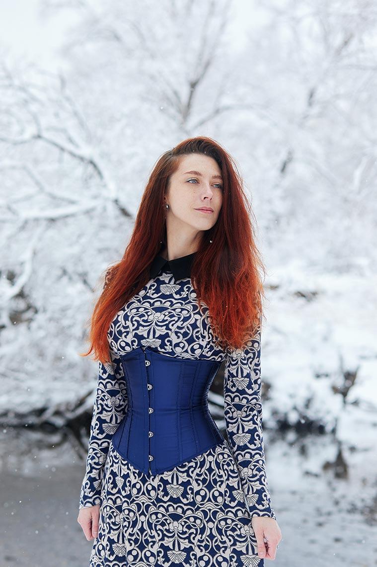 Рыжая женщина в синем корсете