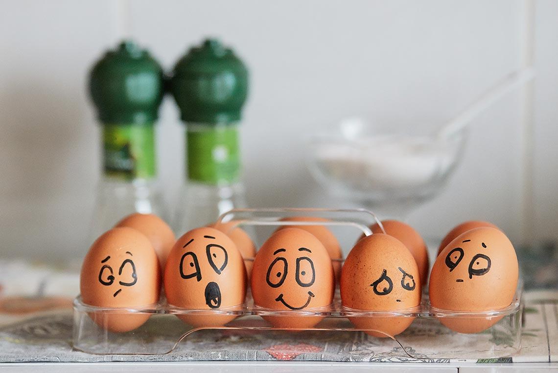 Фон с эмоциональными яйцами с улыбкой и депрессией для вебсайта