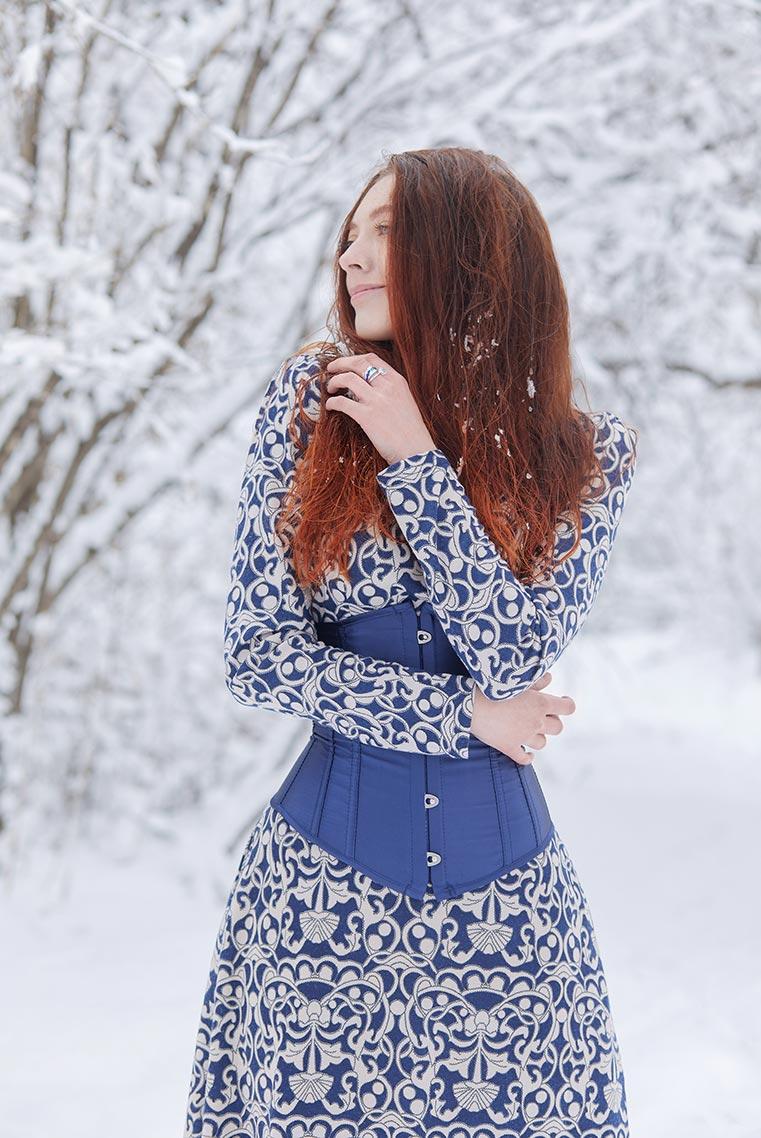 Счастливая женщина позирует в зимнем лесу