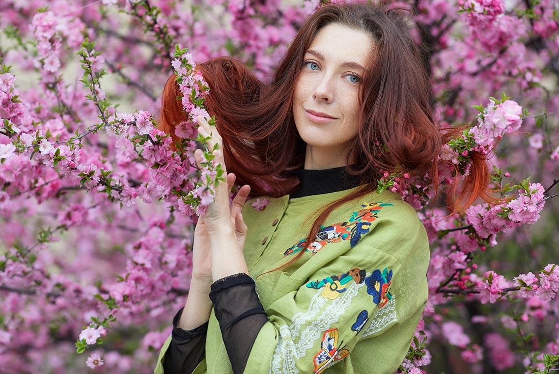 Портрет молодой женщины с длинными рыжими волосами на фоне розовых весенних цветов