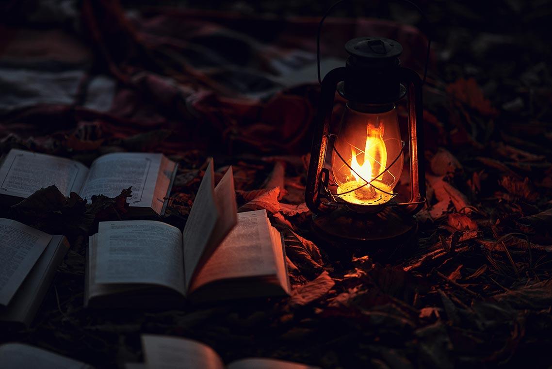 Осенний ночной фон с горящей керосиновой лампой и книгами