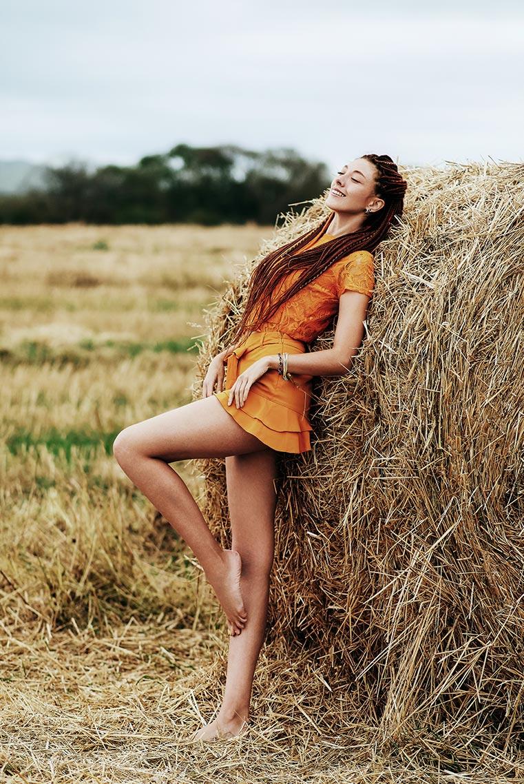 Референс для фотосессии с улыбающейся девушкой на фоне стога сена